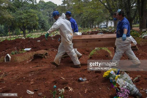 Employees carry the coffin of a person who died suspectedly from COVID19 at the Vila Formosa cemetery in the outskirts of Sao Paulo Brazil on March...