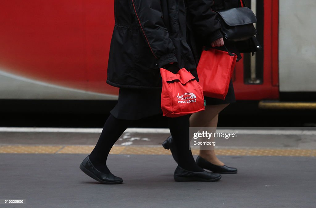 Employees carry Virgin Trains east coast branded bags as they pass along a platform at Kings Cross station, in London, U.K., on Friday, March 18, 2016. Virgin Trains will revive plans to offer high-speed Internet access on Europes busiest rail route in a bid to beat the plane and persuade business people to travel outside peak hours. Photographer: Chris Ratcliffe/Bloomberg via Getty Images