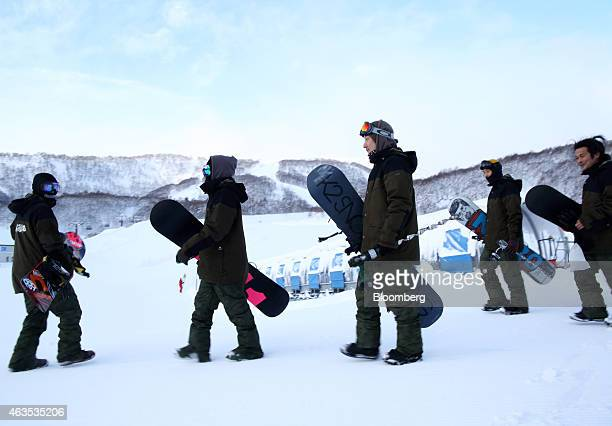 Employees carrying snowboards walk as they go on patrol at the Niseko Hanazono resort operated by Nihon Harmony Resorts KK in Kutchan Hokkaido Japan...