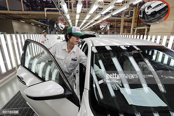 Employees check a Honda Civic vehicle at the quality control station on the production line of the Honda Motor Co assembly plant in Prachinburi...
