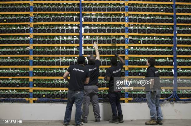 Employees check fans on mining machines at the Bitfarms cryptocurrency farming facility in Farnham, Quebec, Canada, on Wednesday, Jan. 24, 2018. The...