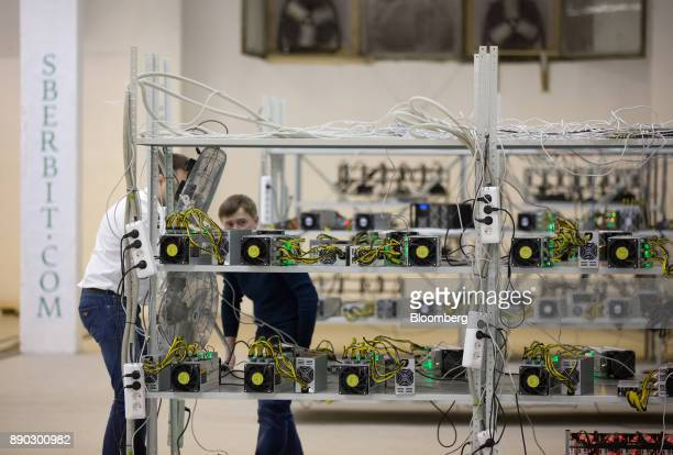 Employees check power supply units and cooling fans linked to cryptocurrency mining machines at the SberBit mining 'hotel' in Moscow Russia on...