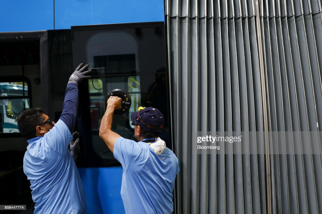 Employees check the fit of a window of an electric bus during production at the BYD Coach and Bus factory in Lancaster, California, U.S., on Thursday, Oct. 5, 2017. BYD unveiled the newly expanded 450,000 square foot factory on Friday, North America's largest electric bus manufacturing facility. Photographer: Patrick T. Fallon/Bloomberg via Getty Images