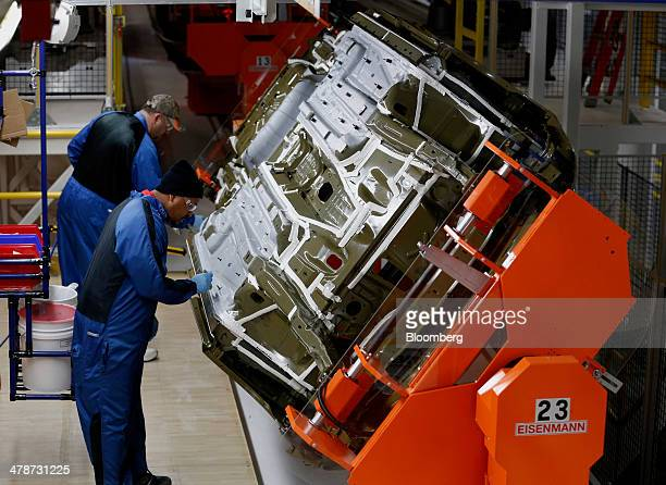 Employees check the under coatings of 2015 Chrysler 200 vehicles in the paint shop at the company's Sterling Heights Assembly Plant in Sterling...
