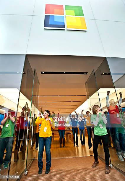 Employees cheer before customers enter at the grand opening of a new Microsoft Store at University Village in Seattle Washington US on Thursday Oct...