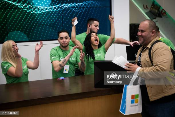 Employees cheer for a customer as he purchases an Xbox One X game console during the Microsoft Corp global launch event in New York US on Monday Nov...