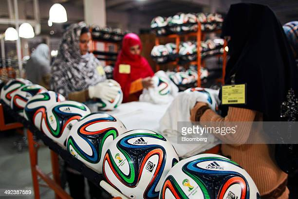 Employees clean Adidas AG 'Brazuca' soccer balls on the production line at the Forward Sports Ltd factory in Sialkot Punjab Pakistan on Tuesday Jan...