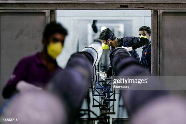Employees clean gas tanks for the Royal Enfield Motors Ltd Classic 350 motorcycle moving on a conveyor on the production line at the company's...