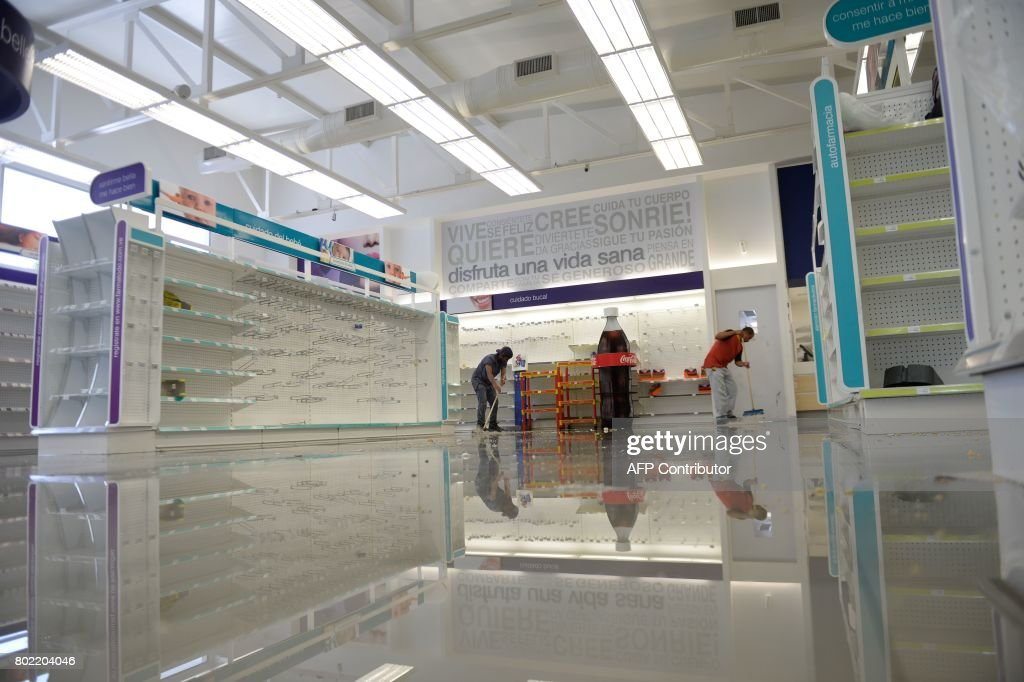 Employees clean the aisles in a looted pharmacy in Maracay, Aragua state, Venezuela on June 27, 2017. /