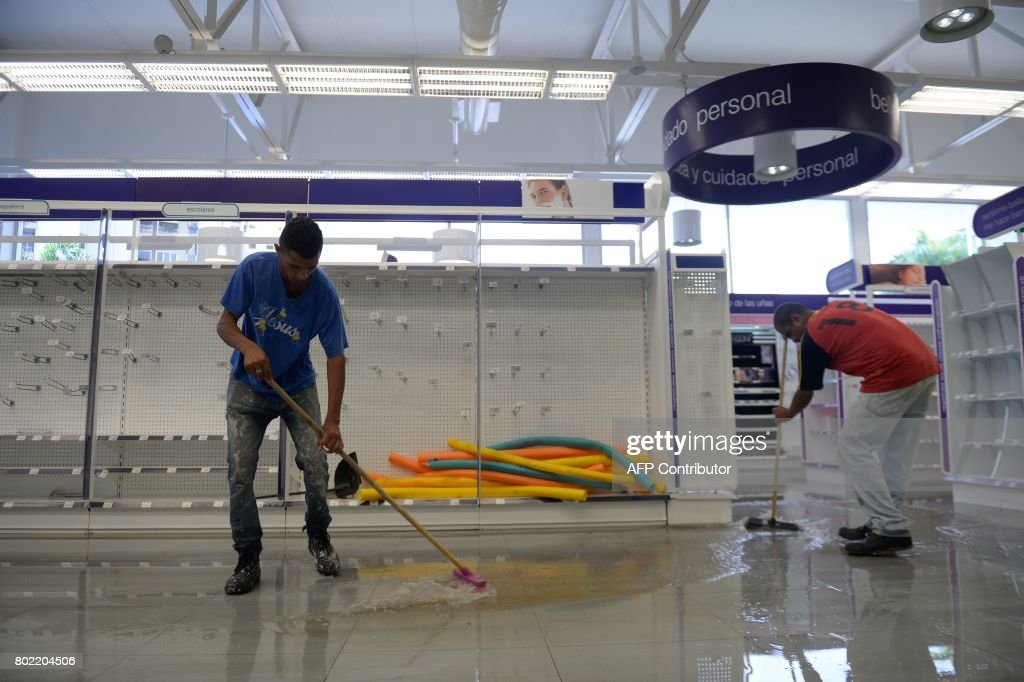 Employees clean the aisles of a looted pharmacy in Maracay, Aragua state, Venezuela on June 27, 2017. /
