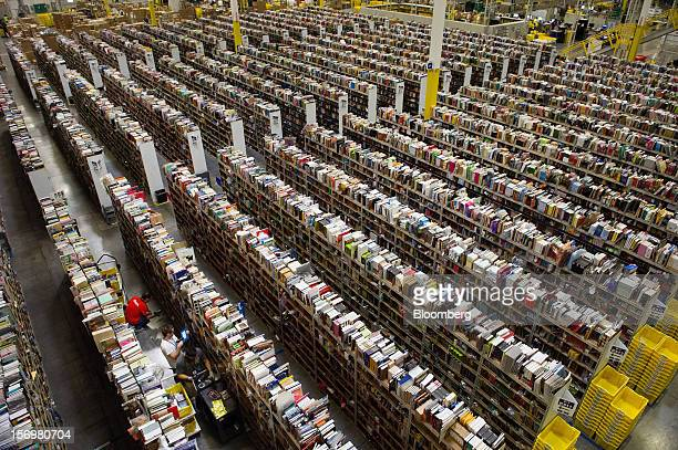 Employees collect merchandise ordered by customers for shipment from the Amazoncom distribution center in Phoenix Arizona US on Monday Nov 26 2012 US...