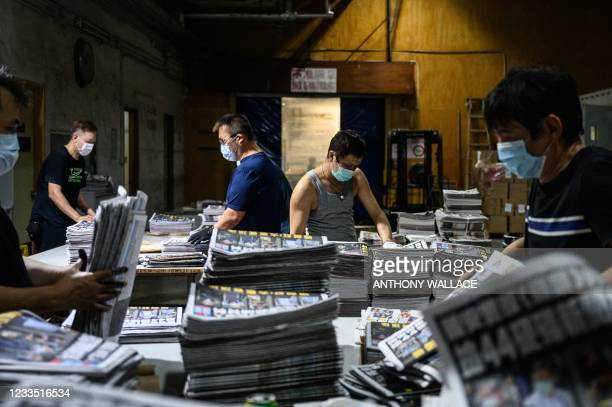 Employees compile different sections of freshly printed papers in the printing facility of the Apple Daily newspaper offices in Hong Kong early on...