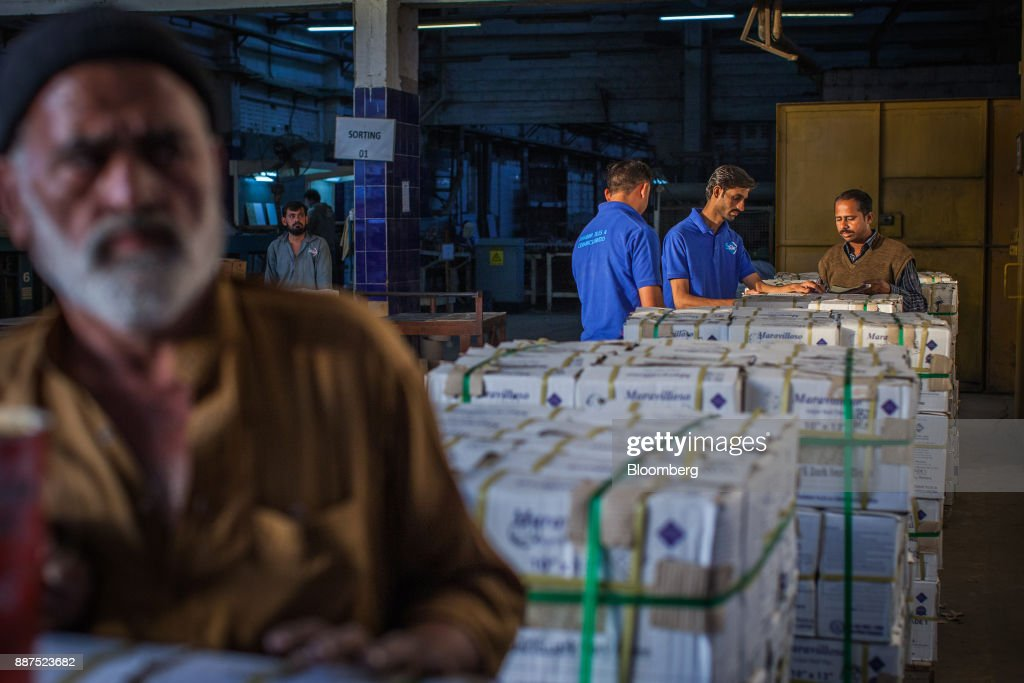 Employees count boxes of tiles before delivery to the warehouse at the Shabbir Tiles & Ceramics Ltd. production facility in Karachi, Pakistan, on Wednesday, Dec. 6, 2017. Shabbir, which had suffered four years of losses while fighting to compete with cheap imports from neighboring China, is on course to post an annual profit next financial year after Pakistan placed an anti-dumping duty on Chinese tiles in October. That follows similar moves from the regulator on steel products. Photographer: Asim Hafeez/Bloomberg via Getty Images