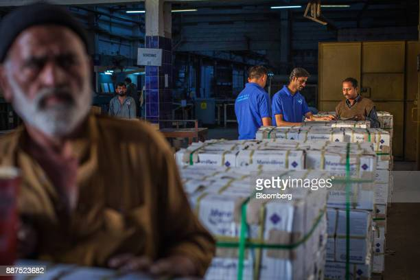 Employees count boxes of tiles before delivery to the warehouse at the Shabbir Tiles Ceramics Ltd production facility in Karachi Pakistan on...