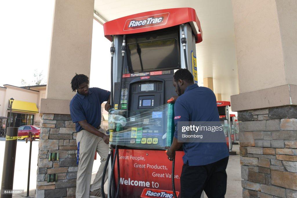 Employees cover a fuel dispenser at RaceTrac Petroleum Inc