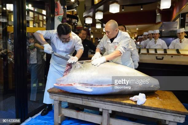 Employees cut a tuna at a Sushi Zanmai restaurant operated by Kiyomura KK in Tokyo Japan on Friday Jan 5 2018 Kiyomura KK operator of Sushi Zanmai...
