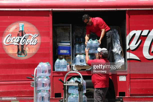 Employees deliver CocaCola Co Dasani brand water bottles to a convenience store in the Miramar neighborhood of San Juan Puerto Rico on Friday Sept 29...