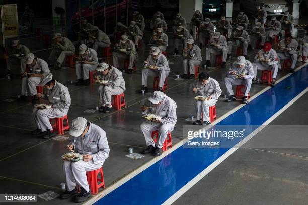 Employees eat their lunch while staying 2 meters away from each other at the Dongfeng Fengshen plant on March 24 2020 in Wuhan Hubei province China...