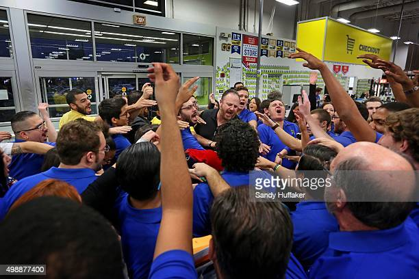 Employees engage in a group cheer before opening their doors to shoppers at a Best Buy on November 26 2015 in San Diego California Although Black...