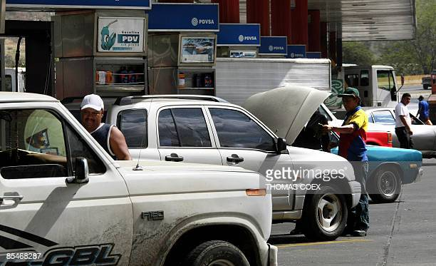 Employees fill up cars in a gas station on March 17, 2009 in Caracas. Venezuela, Latin America's biggest oil producer, is considering hiking its...