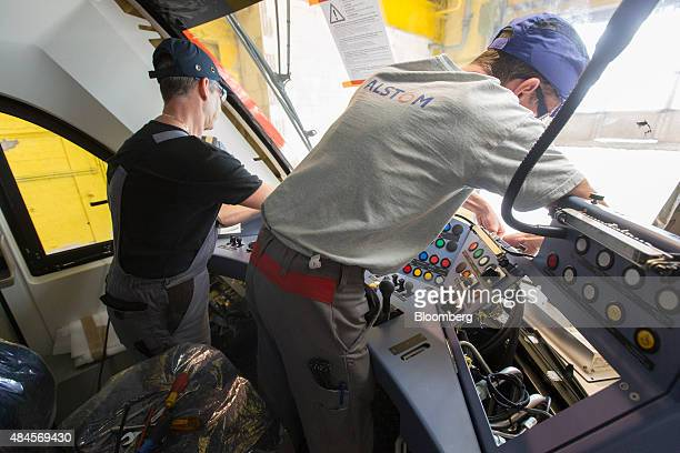 Employees fit a console control panel in the drivers cabin of a Alstom Coradia Lint railway train on the production line of the Alstom SA factory in...