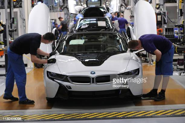 Employees fit a hood to a BMW i8 hybrid electrical automobile at the Bayerische Motoren Werke AG factory in Leipzig Germany on Thursday March 14 2019...