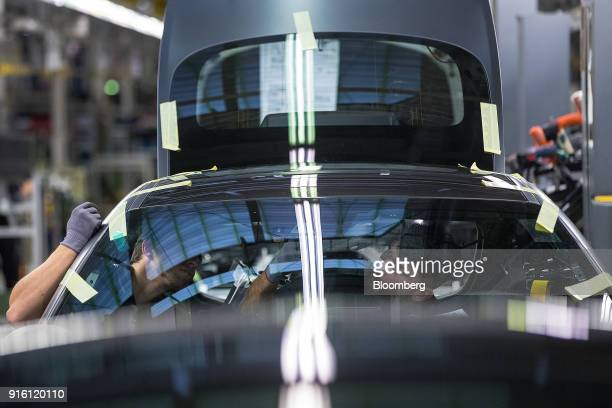 Employees fit interior lights to a MercedesBenz AG AMG GT high performance luxury automobile on the assembly line at the automaker's plant in...