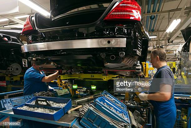 Employees fit suspension parts to a Daimler AG MercedesBenz Sclass automobile as it travels along the production line inside the company's factory in...