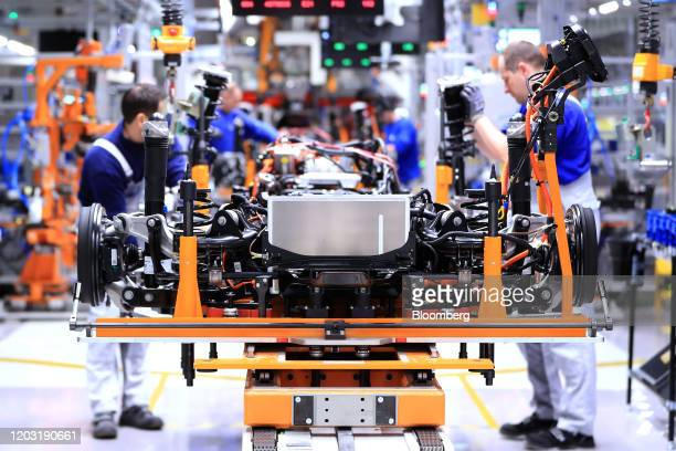 Employees fit suspension units to the chassi of Volkswagen AG ID.3 electric automobiles on the final assembly line at the automaker's factory in...