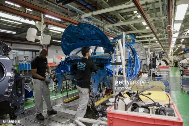 Employees fix cabling inside the body shell of a Renault Zoe automobile on the assembly line inside the Renault SA factory in Flins France on...
