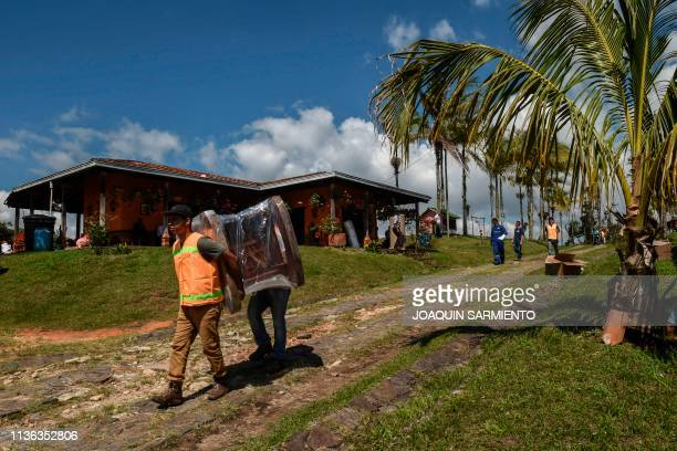 Employees from a moving company carry furniture during an eviction procedure at La Manuela a former vacation estate of late drug kingpin Pablo...