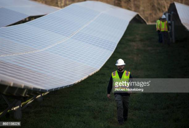 Employees from a Radian Generation's operations and maintenance team change out a faulty solar inverter along a row of solar panels December 4 2017...