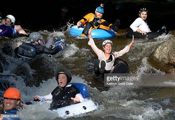 Employees from Boulder's LogRhythm Inc and others don their professional attire and jump in to Boulder Creek on inner tubes and float to work on the...