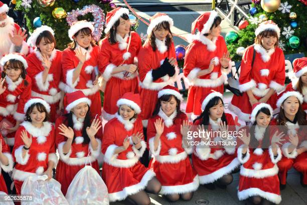 100 employees from Japanese toy makers in Santa Claus costumes gather at a shopping mall on the foot of Tokyo's landmark Skytree on December 10 2016...