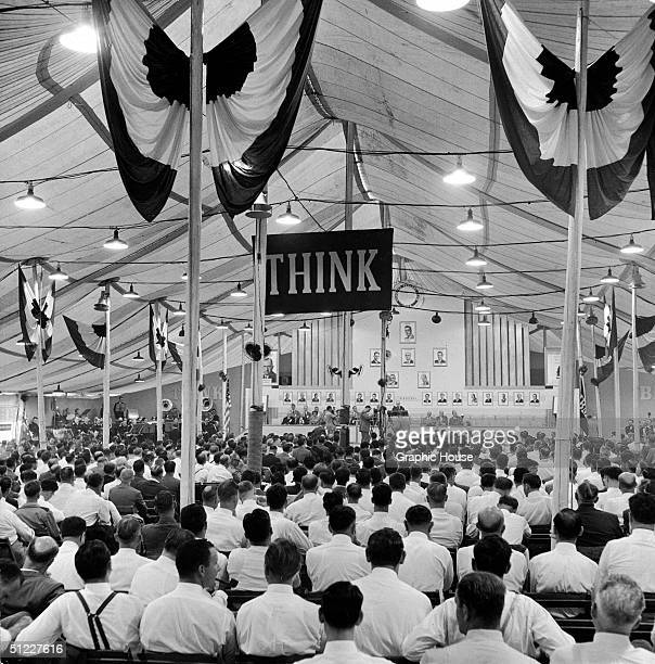 IBM employees gather under a tent during a 'One Hundred Percenter Convention' to listen to speakers at a podium Johnson City New York New York 1947 A...