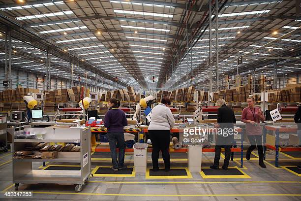 Employees gift wrap items before dispatching them in the huge Amazon 'fulfilment centre' warehouse on November 28 2013 in Peterborough England The...