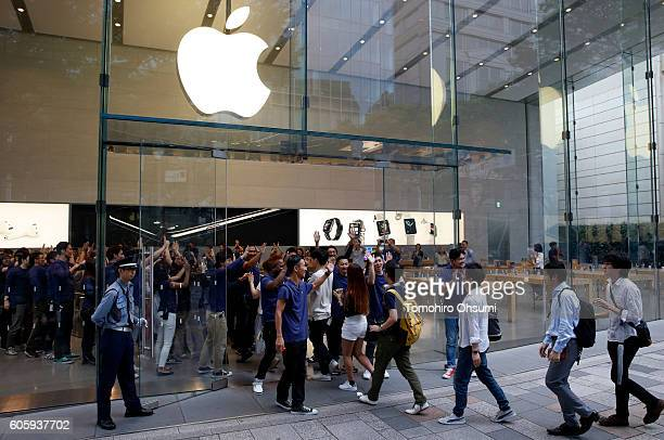Employees give highfives to customers as they enter the Apple Omotesando store during the launch of Apple Inc iPhone 7 and Apple Watch Series 2 on...