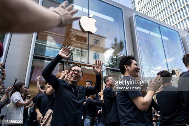 Employees give highfives to customers waiting outside the Apple Marunouchi store on September 07 2019 in Tokyo Japan Apple Inc opened its largest...