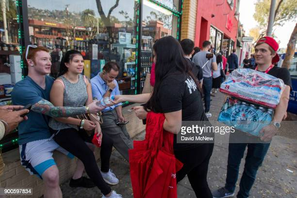 Employees give water to people waiting in line to get into MedMen one of the two Los Angeles area pot shops that began selling marijuana for...