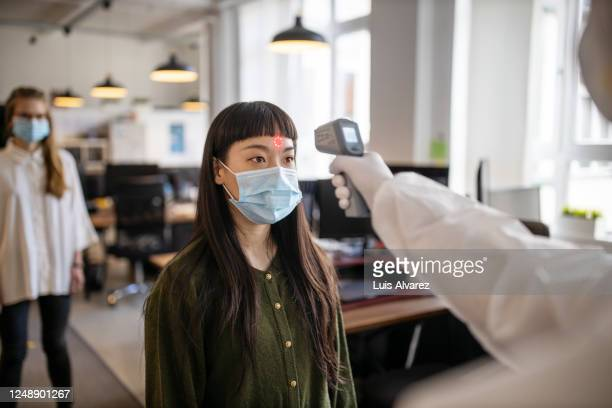 employees going through mandatory temperature checks in office - 感染症 ストックフォトと画像