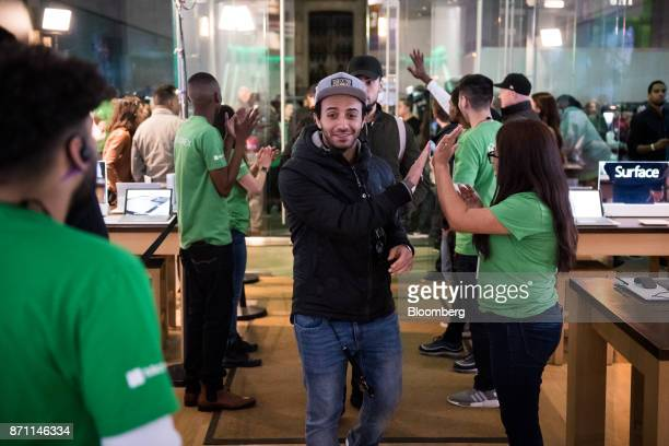 Employees greet customers as they enter the store to prepay for an Xbox One X game console ahead of it's midnight release during the Microsoft Corp...