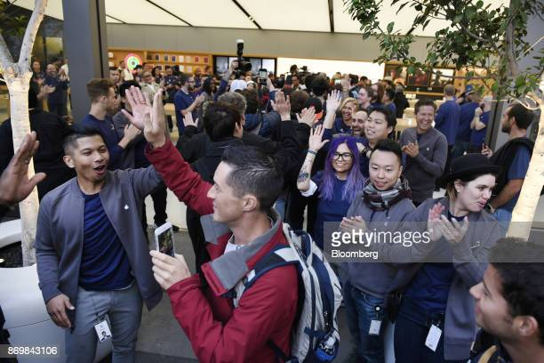 Employees greet customers entering the store during the sales launch for the Apple Inc iPhone X smartphone in San Francisco California US on Friday...