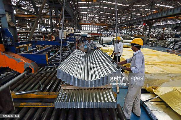 Employees guide finished corrugated steel roofing onto a pallet in the tube mill at the manufacturing facility of Uttam Galva Steels Ltd the Indian...