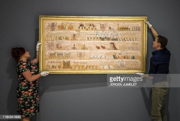 Employees hang a piece of art at the Design Museum Den Bosch for an exhibition entitled Design of the Third Reich in 's-Hertogenbosch, central...