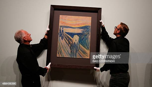 Employees hang the painting 'The Scream' of Norwegian painter Edvard Munch onto a wall for the 'Munch Van Gogh' exhibition at the Van Gogh Museum in...