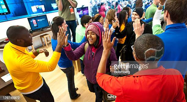 Employees highfive customers as they enter at the grand opening of a new Microsoft Store at University Village in Seattle Washington US on Thursday...
