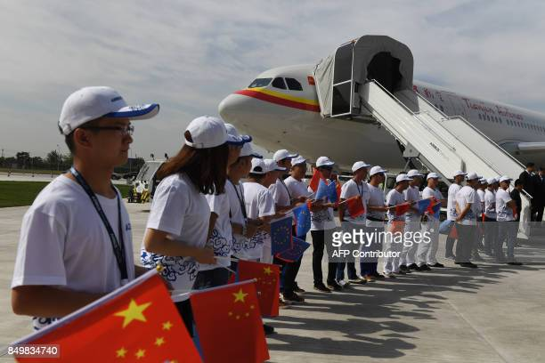 Employees hold flags below the first Airbus A330 plane to be delivered by the Airbus Long Range Cabin Completion Centre during the inauguration...