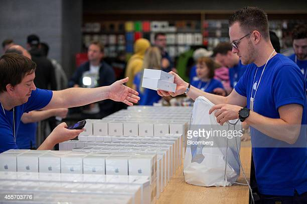 Employees hold packaged iPhones during the sales launch of the iPhone 6 and iPhone 6 Plus smartphones at the Apple Inc store in Berlin Germany on...