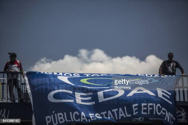 Employees hold up a banner during a protest against the privatization of the State's water and sewage utility outside Cia Esadual de Aguas e Esgotos...