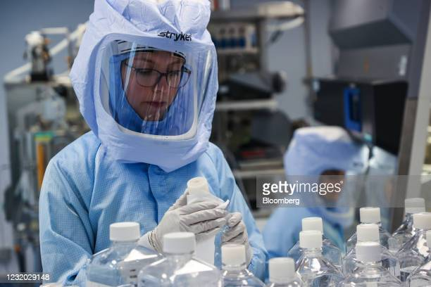 Employees in biohazard suits prepare raw materials for messenger RNA , the first step of Covid-19 vaccine production, at the BioNTech SE laboratory...